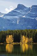 Autumn trees reflected on lake with rocky mountains in banff Stock Photos