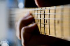 hand on guitar fretboard - stock photo