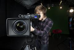 man looks into viewfinder of a tv studio camera - stock photo