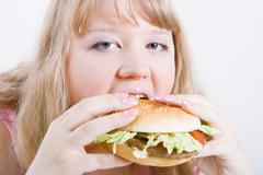 Fat girl with a hamburger Stock Photos
