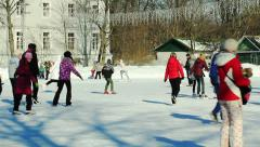 People are skating on the open skating ring on a sunny day Stock Footage