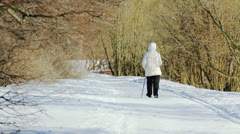 A woman is walking in the park with the help of ski-sticks Stock Footage