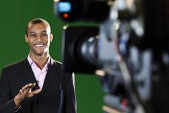 presenter in tv studio with foreground camera - stock photo