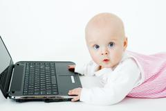 baby with laptop in studio - stock photo