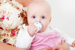 infant with a pacifier - stock photo