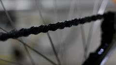 Cleaning greasy bicycle chain with white cloth - stock footage