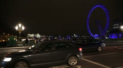 London Eye at night with Westminster Bridge traffic - stock footage