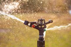 lawn sprinkler spraying water over green grass - stock photo