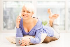 smiling woman with mug on the floor while phoning - stock photo