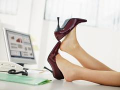 Business woman taking off shoes Stock Photos