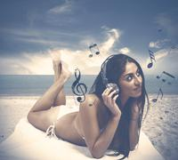Girl listens to music at the beach - stock photo