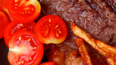 Beef steak on dark plate with red hot chili pepper Stock Footage