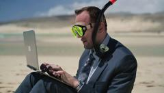 Businessman in diving mask working on laptop on the beach HD Stock Footage