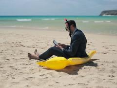 Businessman in diving mask working on tablet computer on the beach NTSC Stock Footage