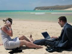 Business people with laptop and cellphone on beautiful beach NTSC - stock footage