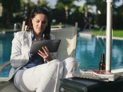 Businesswoman on sunbed using tablet computer by the pool NTSC Stock Footage