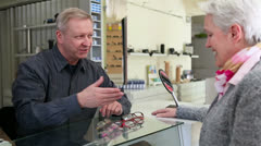 optician selling glasses to senior woman - stock footage