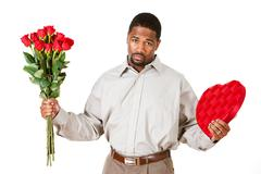 couple: man apologizing with gifts - stock photo