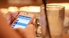 Female hand Typing / texting and sending a SMS message on a smartphone in a bar. Stock Footage