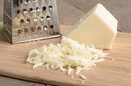 Parmesan cheese grated on a cutting board Stock Photos