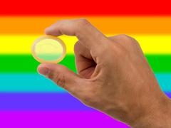 male giving a condom, rainbow flag pattern - stock photo