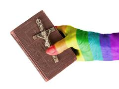 Old hand (woman) holding a very old bible, rainbow flag Stock Photos