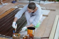 happy woman paints the wood - stock photo