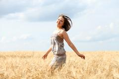 Stock Photo of happy woman in golden wheat