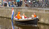 Stock Photo of typical orange dressed dutchmen in a boat on queen's day