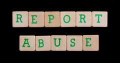green letters on old wooden blocks (report abuse) - stock photo