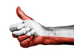 Old woman with arthritis giving the thumbs up sign, wrapped in flag pattern Stock Photos
