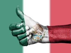 old woman with arthritis giving thumbs up sign, wrapped in mexico flag pattern - stock photo