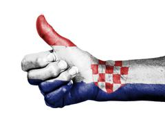 Stock Photo of old woman with arthritis giving the thumbs up sign, wrapped in flag pattern