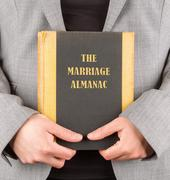 Woman holding a marriage almanac Stock Photos