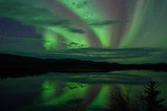 Night sky stars and northern lights mirrored] Stock Photos