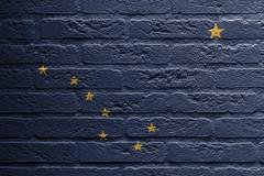 Stock Illustration of brick wall with a painting of a flag, alaska