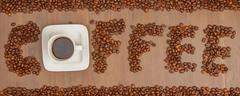 the word coffee spelled with hundreds of coffee beans and one cup of coffee - stock photo