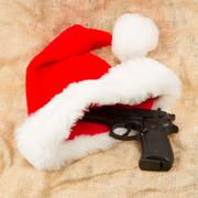 Weapon (firearm) concealed in santas hat Stock Photos