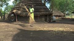 Didinga girl sweeps the ground near her Home Stock Footage