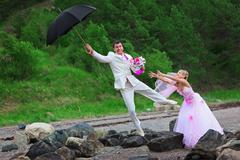 Groom with umbrella and bride - wedding joke Stock Photos