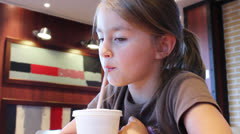 Nice young girl  drinks from plastic cup through straw - stock footage