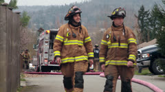 Firefighters shaking hands, fire engine, fire hose - stock footage