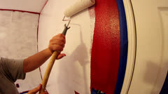 Close up of roller with white paint going on red wall Stock Footage