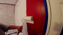 Slow motion closeup of white paint rolled onto red wall. Stock Footage