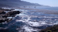 Waves crashing against the rocky coastline of Big Sur, California - stock footage