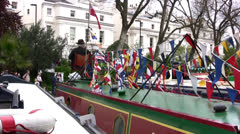 Man sitting on top of barge decorated with flags in Regents canal, London Stock Footage