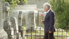 Tracking shot of elderly man walking in graveyard Stock Footage