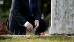 Elderly man kneeling down to lay flower on grave - stock footage