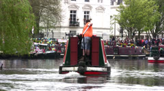 Crewman steering barge along a canal in London Stock Footage