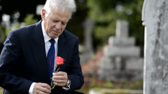 Sad elderly man lays flower on grave, looks at headstone - stock footage